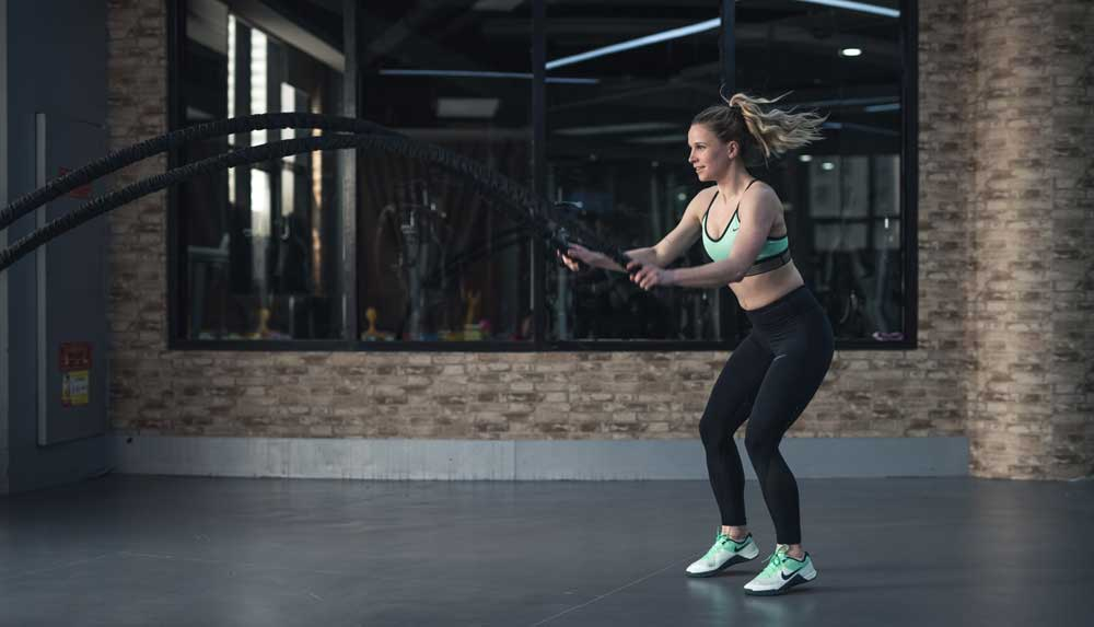 woman in gym attire doing battle rope exercises